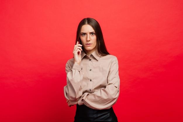 Surpris jeune femme à l'aide de téléphone intelligent sur l'espace rouge