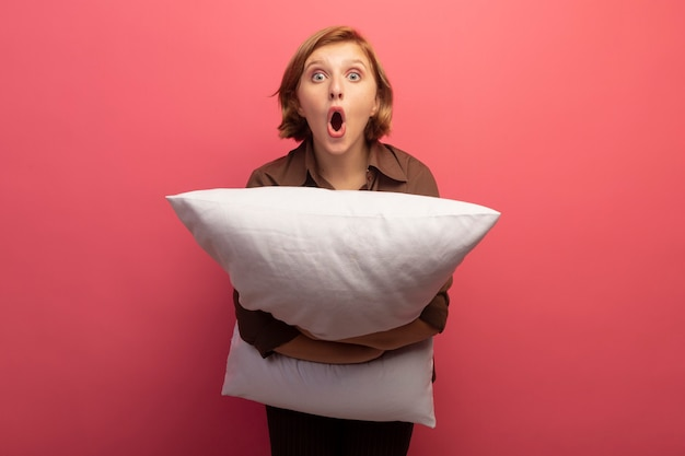Surpris jeune femme blonde étreignant un oreiller regardant à l'avant isolé sur un mur rose avec espace pour copie