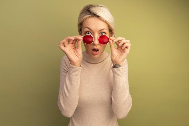 Surpris jeune femme blonde portant et saisissant des lunettes de soleil regardant à l'avant isolé sur un mur vert olive avec espace de copie