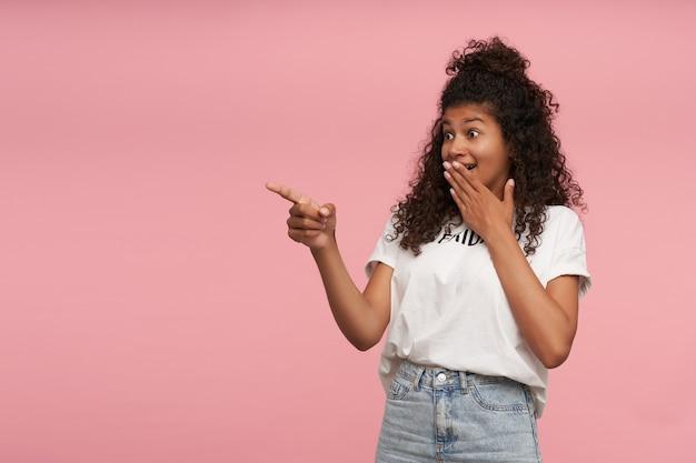 Surpris jeune femme brune aux cheveux longs bouclés avec la peau foncée arrondissant les yeux et la bouche coning avec la paume surélevée, pointant de côté avec l'index tout en posant sur le rose