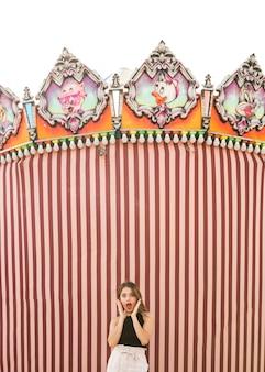 Surpris jeune femme debout devant la tente au parc d'attractions