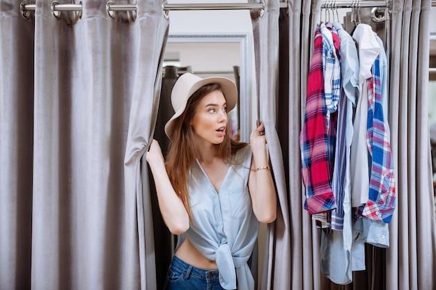 Surpris jeune femme essayant des vêtements et à la recherche de vestiaire