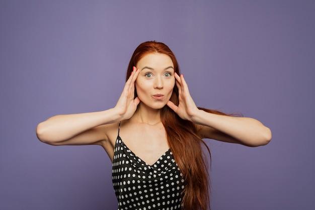 Surpris, une jeune femme heureuse se tient sur le mur violet, heureuse de voir de grandes remises sur les vêtements, exprime le choc, garde les mains près de la tête, la mâchoire baissée, va dépenser beaucoup d'argent aujourd'hui