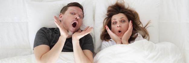 Surpris jeune femme et homme allongé dans le lit vue de dessus confortable concept de matelas orthopédiques