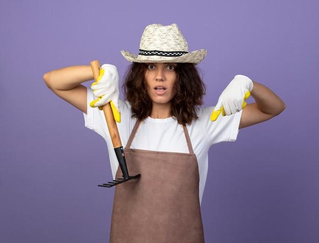 Surpris jeune femme jardinière en uniforme portant chapeau de jardinage et gants tenant des points de râteau vers le bas