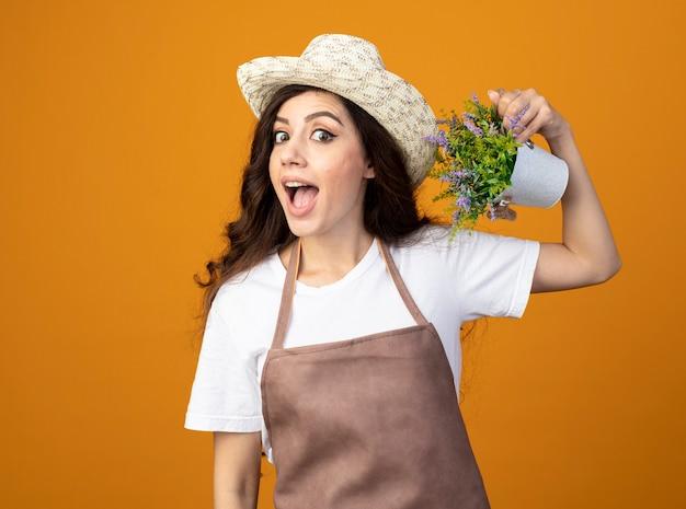 Surpris jeune femme jardinière en uniforme portant chapeau de jardinage tenant pot de fleurs isolé sur mur orange avec espace copie
