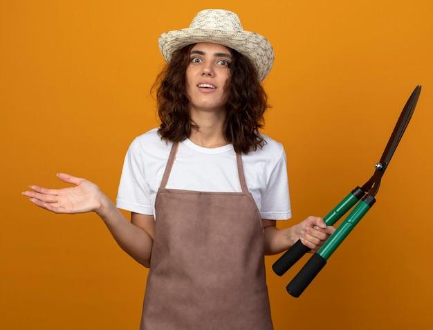 Surpris jeune femme jardinière en uniforme portant chapeau de jardinage tenant des tondeuses et répandre la main