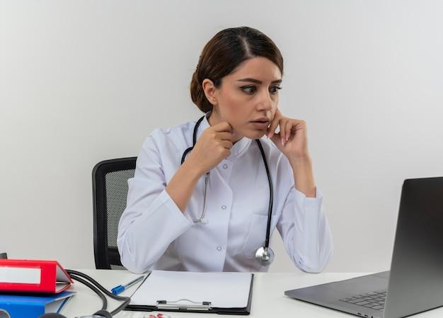 Surpris jeune femme médecin portant une robe médicale avec stéthoscope assis au bureau de travail sur ordinateur avec des outils médicaux en regardant un ordinateur portable avec copie espace