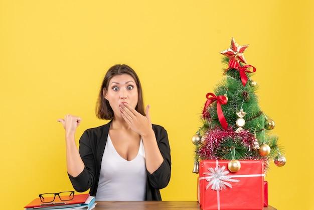 Surpris jeune femme pointant derrière en costume près de sapin de noël décoré au bureau sur jaune