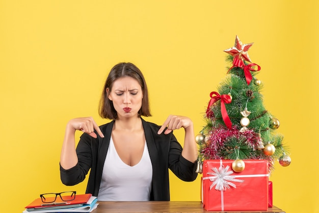 Surpris jeune femme pointant vers le bas en costume près de sapin de noël décoré au bureau sur jaune