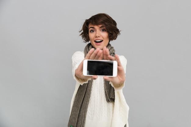 Surpris de jeune femme portant un foulard montrant l'affichage du téléphone mobile.