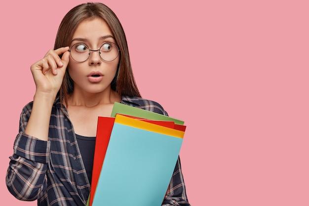 Surpris jeune femme posant contre le mur rose avec des lunettes