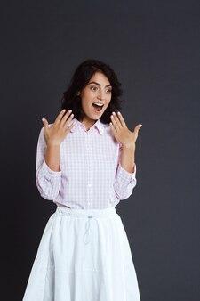 Surpris de jeune femme posant sur un mur gris
