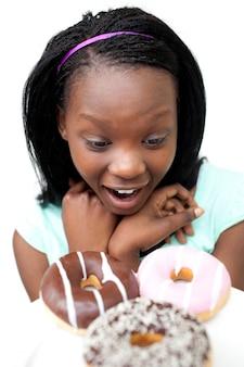 Surpris jeune femme regardant des beignets