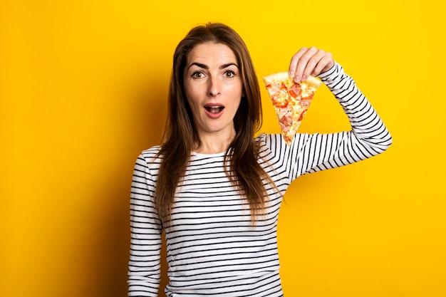 Surpris jeune femme regarde tenant une tranche de pizza fraîche chaude sur un jaune.