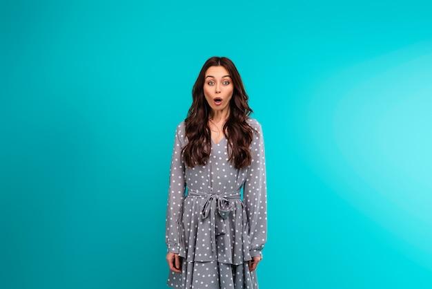 Surpris jeune femme en robe d'été isolée sur fond bleu turquoise