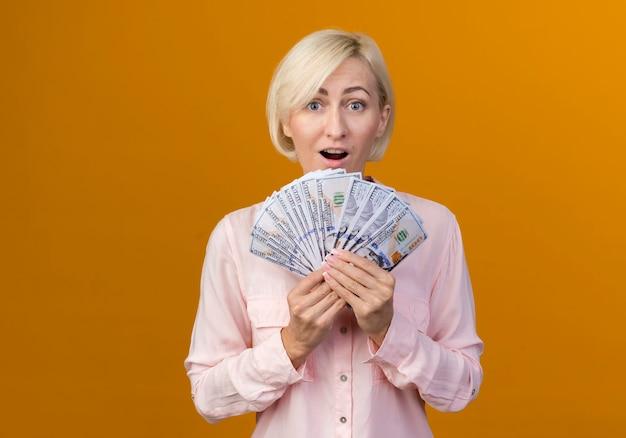 Surpris jeune femme slave blonde tenant de l'argent isolé sur un mur orange