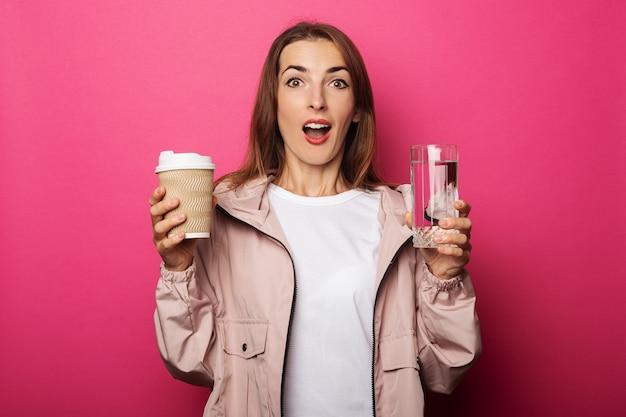 Surpris jeune femme tenant une tasse en papier et une tasse en verre avec de l'eau o
