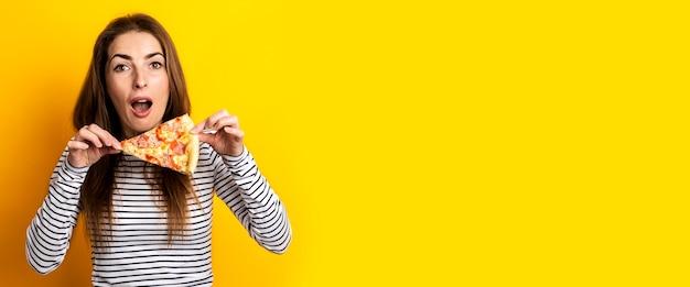 Surpris jeune femme tenant une tranche de pizza fraîche sur un jaune