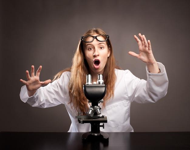 Surpris jeune femme travaillant avec un microscope