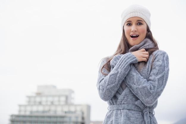 Surpris de jeune femme avec des vêtements d'hiver sur posant