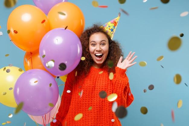 Surpris jeune fille afro-américaine en chapeau d'anniversaire de vêtements tricotés orange isolé sur un mur bleu pastel. concept de fête de vacances. célébrer avec des confettis, des ballons à air colorés écartant les mains.