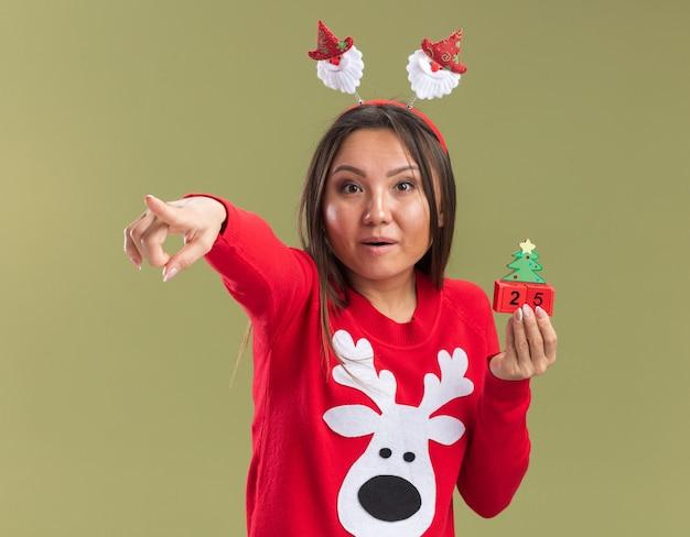 Surpris jeune fille asiatique portant des cerceaux de cheveux de noël tenant des points de jouets de noël à la caméra isolée sur fond vert olive