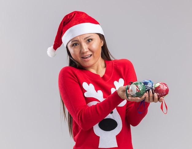 Surpris jeune fille asiatique portant chapeau de noël avec chandail tenant des boules de sapin de noël isolé sur fond blanc