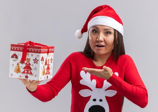 Surpris jeune fille asiatique portant un chapeau de noël avec chandail tenant et points à boîte-cadeau isolé sur mur blanc