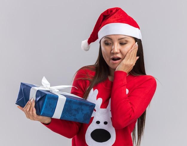 Surpris jeune fille asiatique portant chapeau de noël avec chandail tenant et regardant la boîte-cadeau mettant la main sur la joue isolé sur fond blanc
