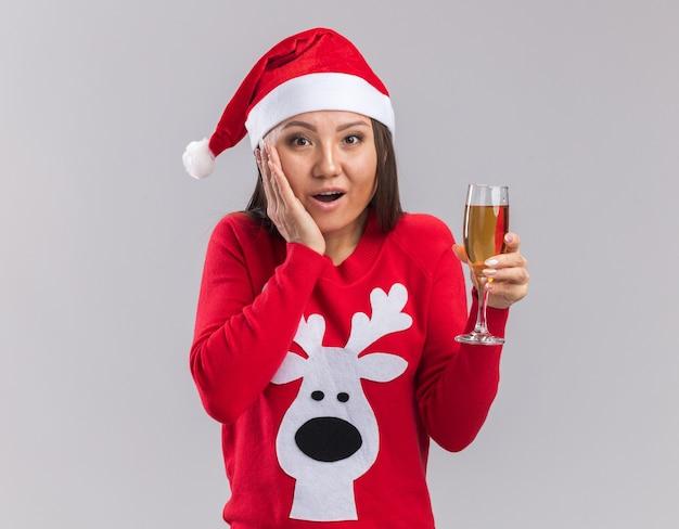 Surpris jeune fille asiatique portant chapeau de noël avec chandail tenant un verre de champagne mettant la main sur la joue isolé sur fond blanc