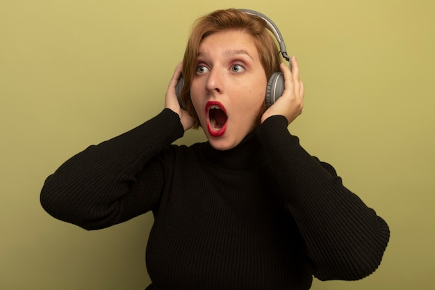 Surpris jeune fille blonde portant des écouteurs mettant les mains sur eux à tout droit