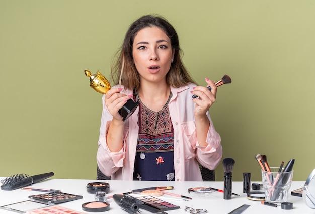 Surpris jeune fille brune assise à table avec des outils de maquillage tenant un pinceau de maquillage et une coupe gagnante isolée sur un mur vert olive avec espace pour copie