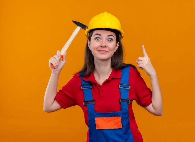 Surpris jeune fille de constructeur tient le marteau et pointe sur fond orange isolé