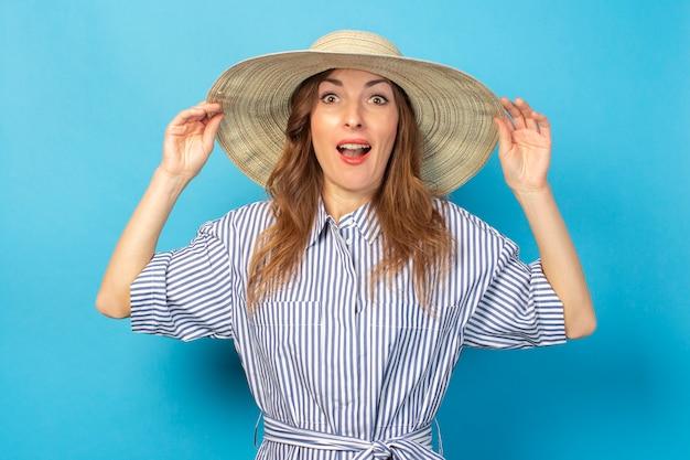 Surpris de jeune fille dans une robe et un chapeau, tient un chapeau avec les mains sur un mur bleu. concept de vacances, d'été et de voyage