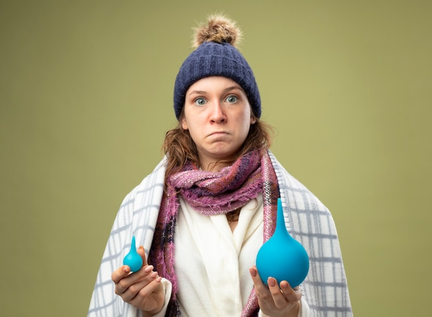Surpris jeune fille malade portant une robe blanche et un chapeau d'hiver avec écharpe enveloppée dans un plaid tenant des lavements isolés sur vert olive