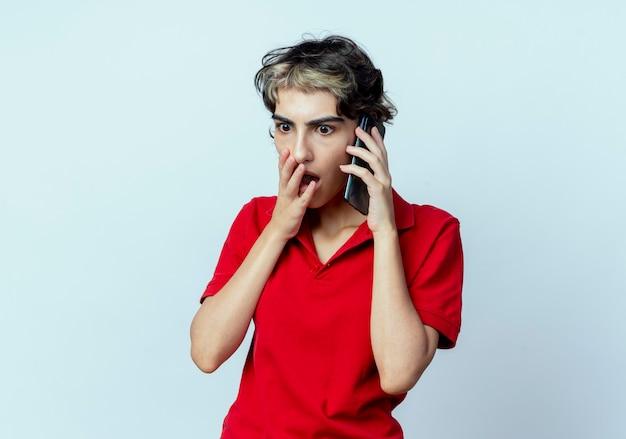Surpris jeune fille de race blanche avec coupe de cheveux de lutin, parler au téléphone, mettre la main sur la bouche regardant vers le bas isolé sur fond blanc avec espace de copie