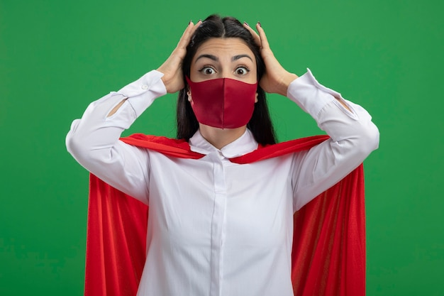 Surpris jeune fille de super-héros caucasien portant un masque mettant les mains sur sa tête en regardant la caméra isolée sur fond vert