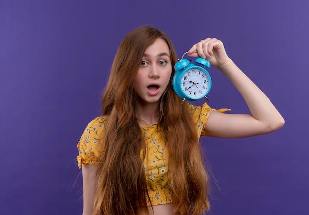 Surpris jeune fille tenant un réveil sur un mur violet isolé