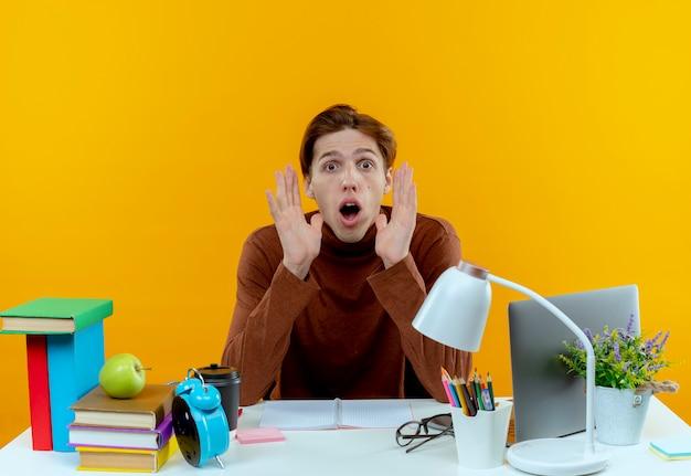 Surpris jeune garçon étudiant assis au bureau avec des outils scolaires tenant les mains autour du visage