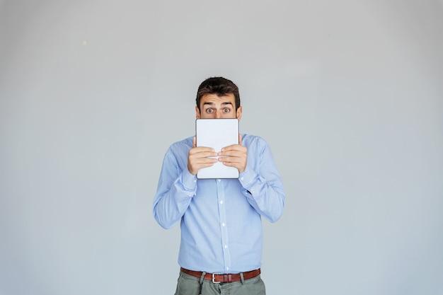 Surpris jeune homme d'affaires tenant la tablette et se cachant derrière.