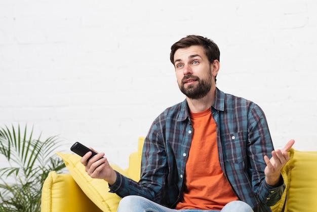 Surpris jeune homme assis sur un canapé