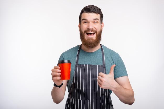 Surpris jeune homme barbu portant un tablier tient sa tasse pour aller tout en souriant et en montrant le pouce sur le mur blanc