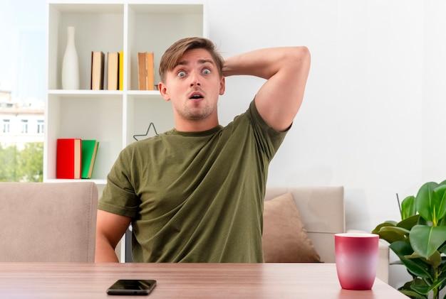 Surpris jeune homme beau blond est assis à table avec téléphone et tasse mettant la main sur la tête derrière en regardant la caméra à l'intérieur du salon