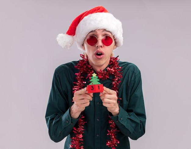 Surpris jeune homme blond portant bonnet de noel et lunettes avec guirlande de guirlandes autour du cou tenant un jouet d'arbre de noël avec date regardant la caméra isolée sur fond blanc