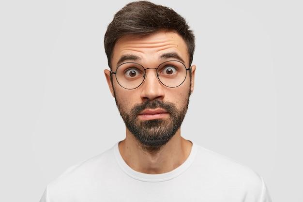 Surpris, un jeune homme étonné regarde avec des yeux écarquillés, ne peut pas croire en son échec