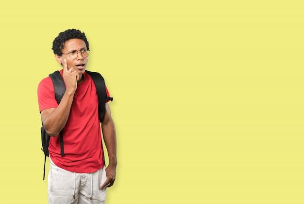 Surpris jeune homme faisant un geste de doute