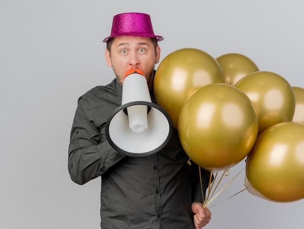 Surpris jeune homme de fête portant un chapeau rose tenant des ballons et parle sur haut-parleur isolé sur blanc