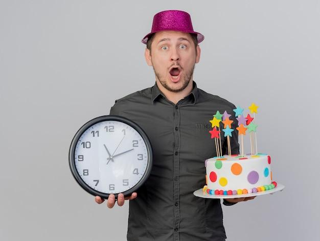Surpris jeune homme de fête portant un chapeau rose tenant une horloge murale avec un gâteau isolé sur fond blanc