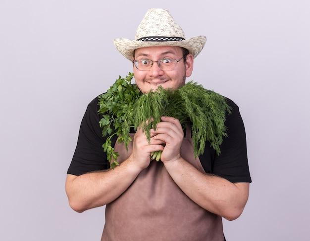 Surpris jeune homme jardinier portant chapeau de jardinage tenant de l'aneth avec de la coriandre autour du visage isolé sur mur blanc